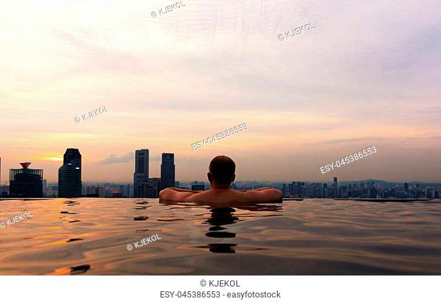 Rear view of man in infinity pool of Marina Bay Skypark looking at city in Singapore at sunset