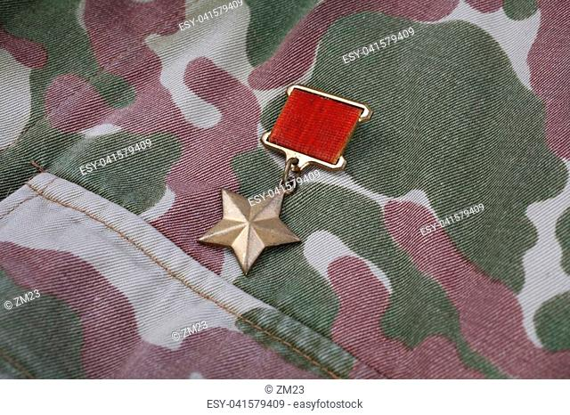 """The Gold Star medal is a special insignia that identifies recipients of the title """"""""Hero"""""""" in the Soviet Union on Soviet camouflage uniform background"""