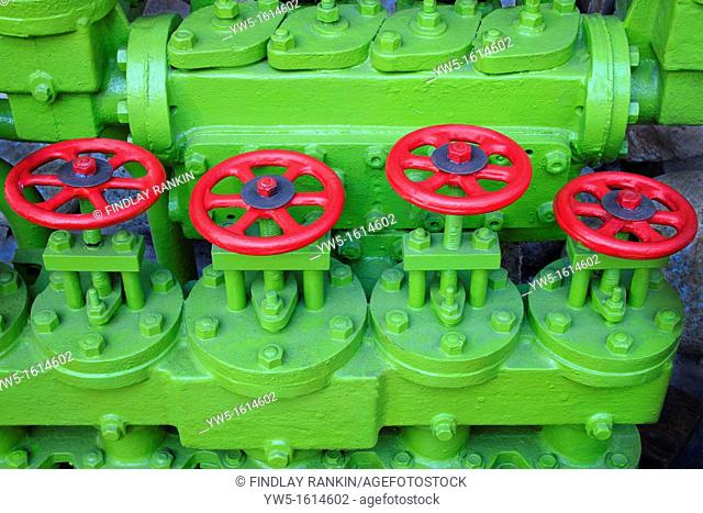 Green painted engine with four red painted round handled valve controls