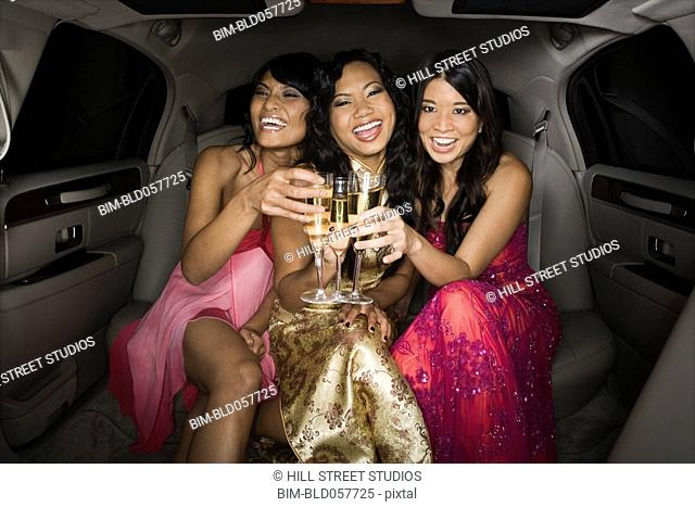 Multi-ethnic women toasting in limousine