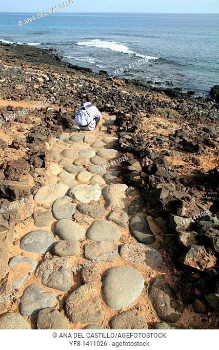 Man sitting on ground Small island of Lobos near Fuerteventura Canary islands Spain