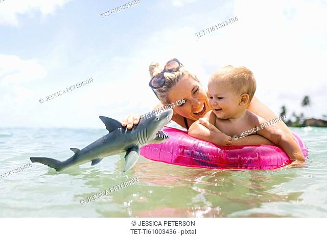 Mother playing with son (12-17 months) in sea