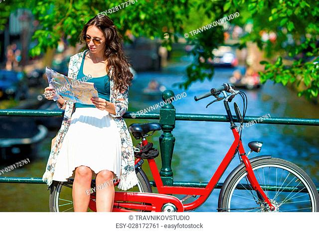 Happy young woman with a city map smiling riding on bicycle