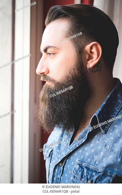 Young bearded man looking out of window