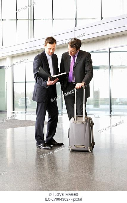 Two businessmen discussing business in the foyer of office building
