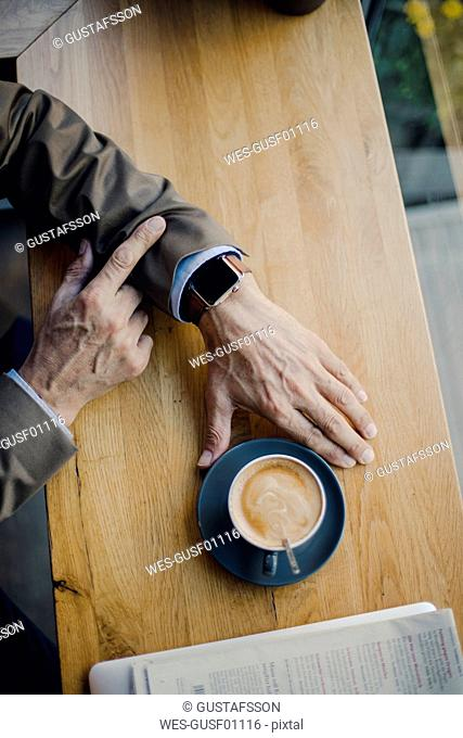 Mature businessman sitting in coffee shop, checking time