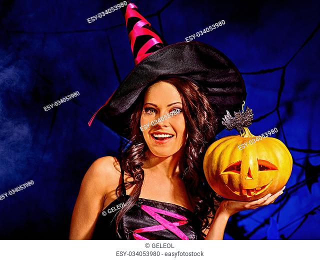 Happy witch holding carving pumpkin