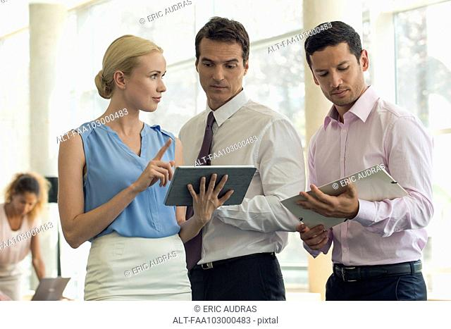 Businesswoman showing colleagues digital tablet