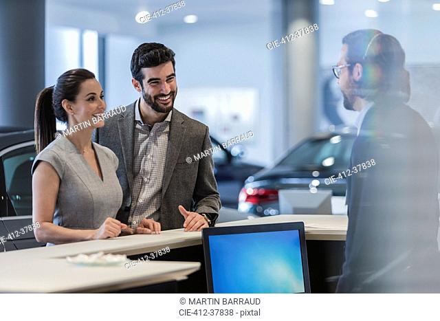 Couple customers talking to receptionist at desk in car dealership showroom
