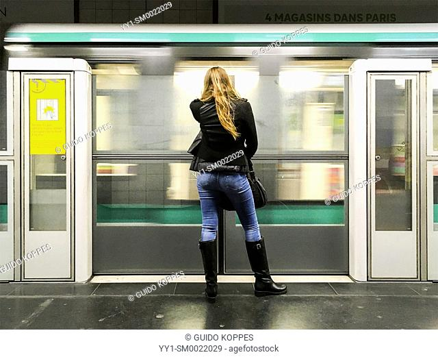 Paris, France. Young adult blonde woman waiting at a subway station's platform for her underground train elsewhere. Subways are often a lifeline throughout...