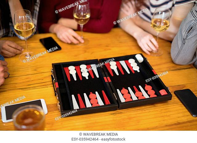 Friends playing backgammon while having glass of wine