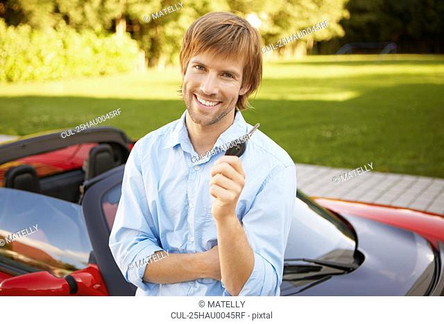 Man proudly showing his key to his car