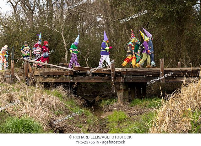 Costumed revelers walk across an old wooden bridge during the Faquetigue Courir de Mardi Gras chicken run on Fat Tuesday February 17, 2015 in Eunice, Louisiana
