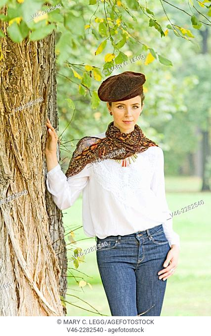 Young woman standing under tree. Woman wearing a bron knit beret and dark scarf with white blouse and blue jeans stands under a large old tree