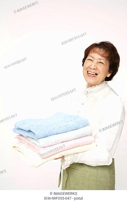 Senior woman holding stack of clean towels