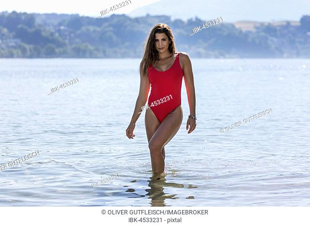Young woman in red bathing suit in shallow water