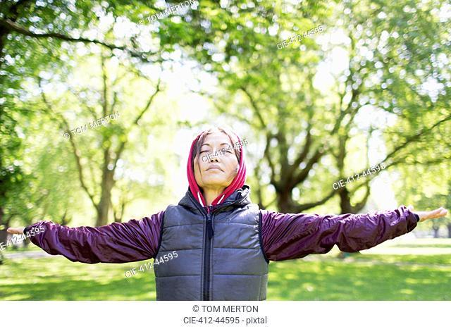 Portrait serene active senior woman stretching in park