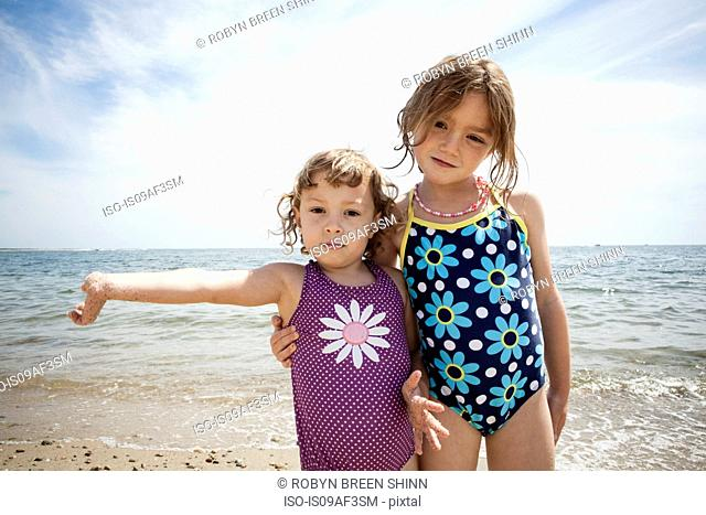 Portrait of two young sisters on beach at Falmouth, Massachusetts, USA