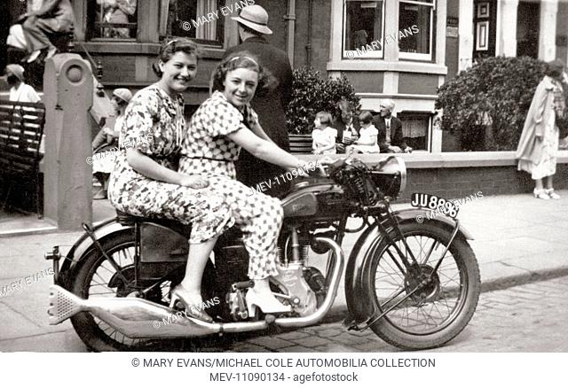 Two ladies sitting on a 1938 Velocette Mov 250cc ohv motorcycle in the street circa 1938