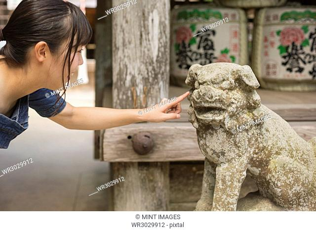 Young woman wearing blue dress touching stone sculpture of lion at Shinto Sakurai Shrine, Fukuoka, Japan