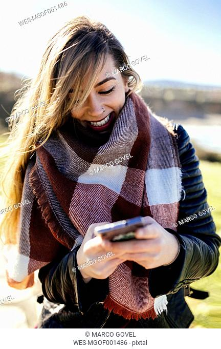 Smiling young woman using smartphone outdoors