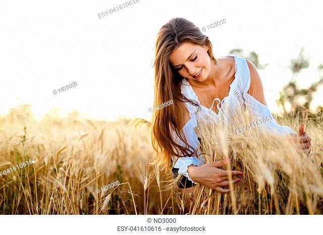 Beautiful woman hugging barley and wheat, concept