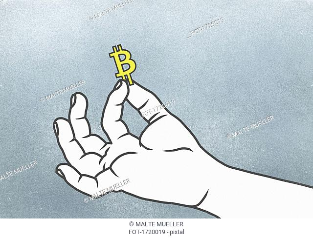 Cropped hand of man holding Bitcoin symbol against gray background