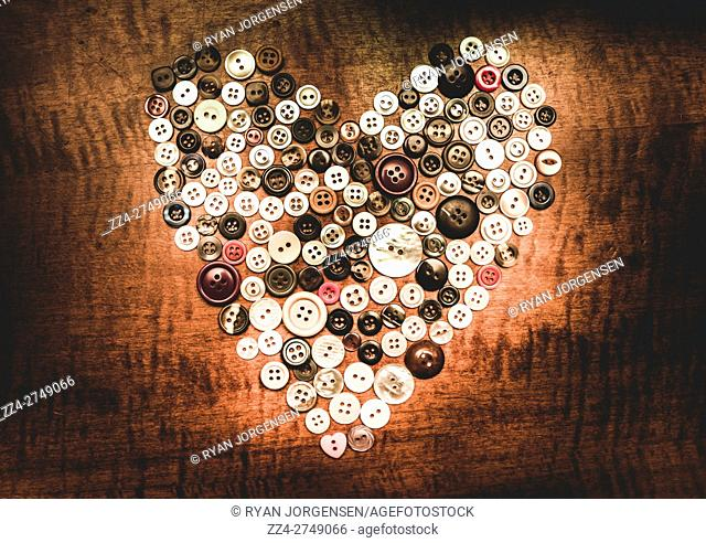 Adorable vintage still-life composition on a variety of clothing buttons arranged in the shape of a heart. Tailor made heart
