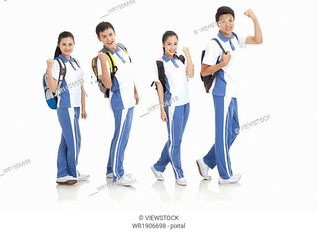 High school students carrying bags do fisting gestures