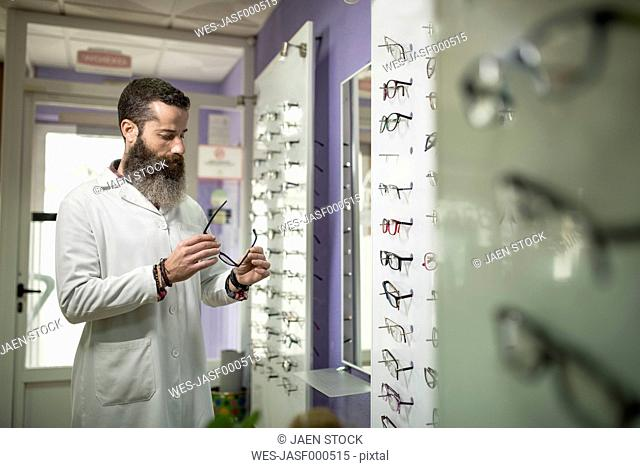 Bearded optometrist in his store looking at glasses