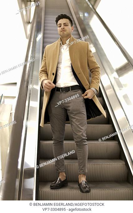 young man on escalator in shopping mall, in Berlin, Germany