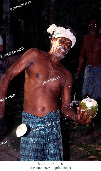 India Kerala indian man cutting a coconut in the backwaters