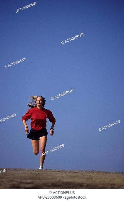 Woman jogging across a field