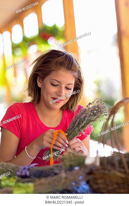 Mixed race girl tying bundle of flowers
