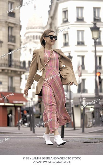 stylish blogger woman crossing street during fashion week, in city Paris, France