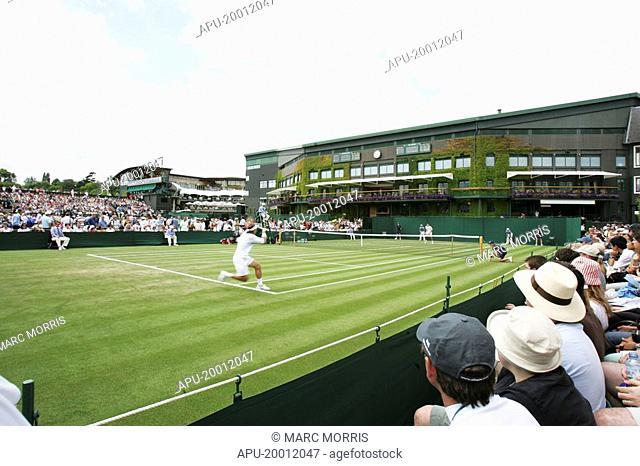 Tennis match being played on a grass court