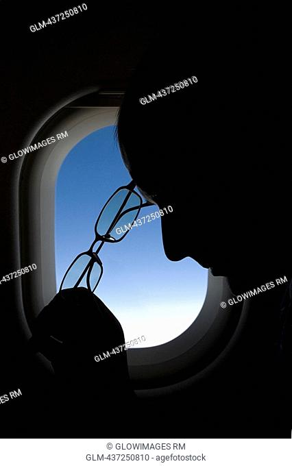 Passenger holding eyeglasses in front of an airplane window