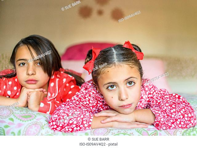 Portrait of two sisters lying on bed gazing