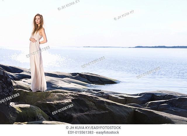 Beautiful young woman wearing white dress, scandinavian shore and sea on background