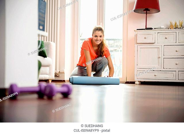 Young woman rolling up exercise mat at home