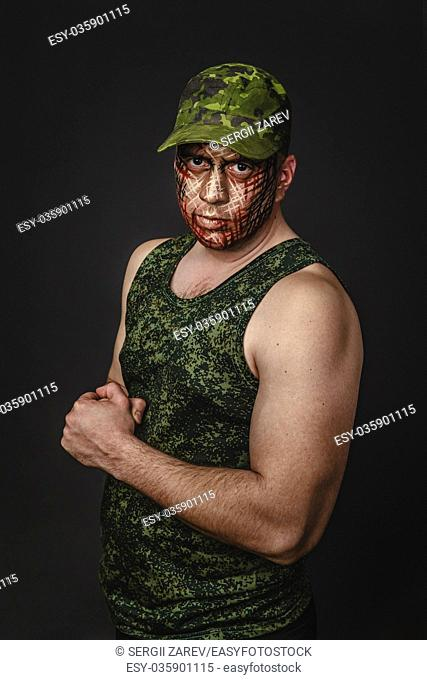 Portrait of Soldier with Military Style Camouflage on a Face. Portrait on black background
