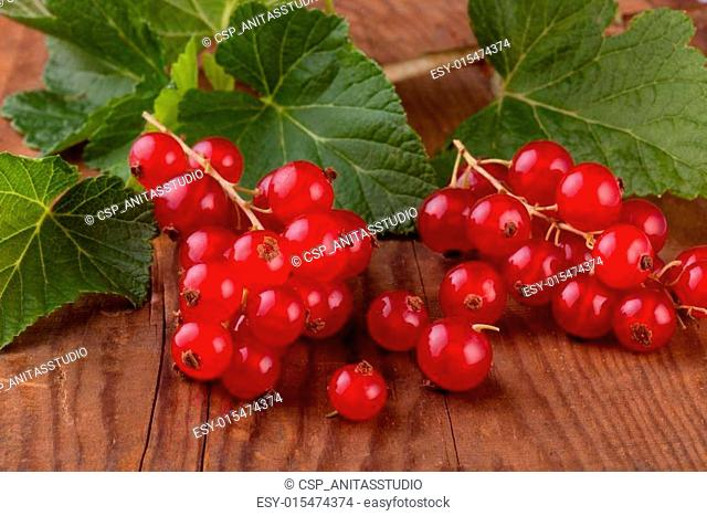 red currant with leaves on wood background