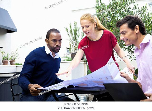 Businesswoman explaining blueprint to colleagues