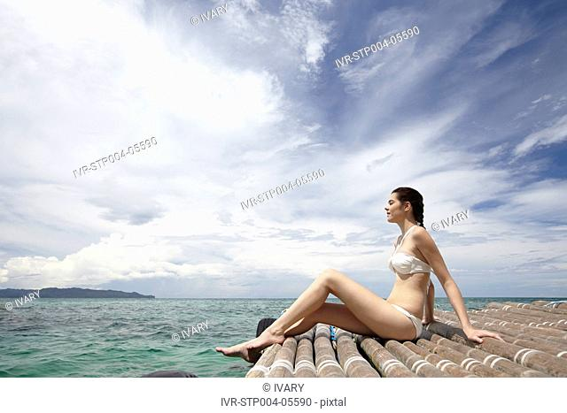 A young woman sitting on a dock by the ocean