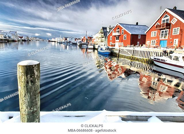 View from the pier on the channel Henningsvaer overlooked by the fishermens houses. Lofoten Islands. Norway. Europe