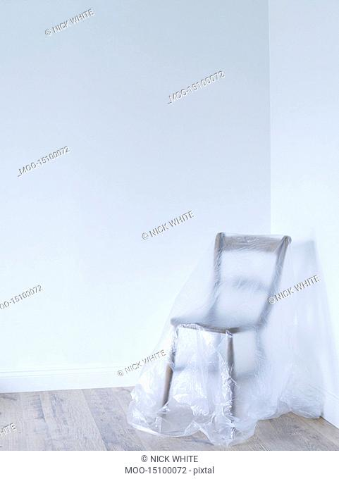 Chair covered by plastic in empty room corner