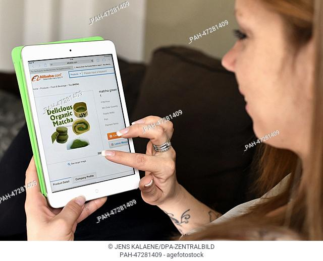 ILLUSTRATION - A young woman browses on her tablet computer through the web page of Chinese online retailer Alibaba looking at offers on green Matcha tea on...