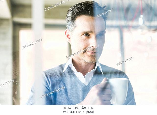Businessman looking at transparant projection screen in office