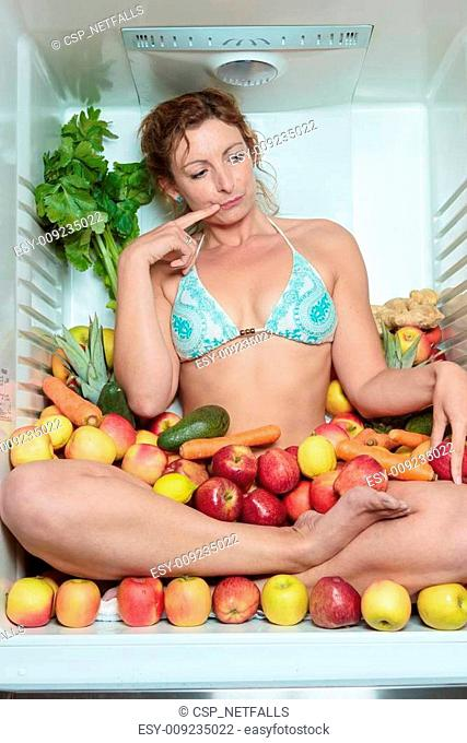 Woman sitting in a fridge in the lotus position