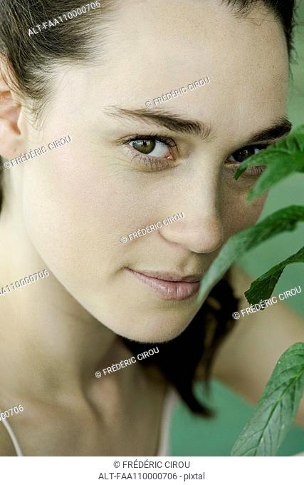 Young woman smelling plant